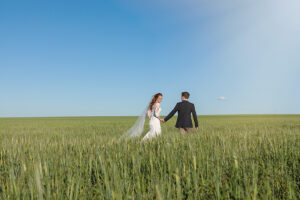 Wedding photography of Bride and Groom walking in a wheat crop