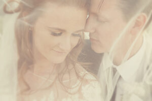Wedding photography of bride and groom under veil